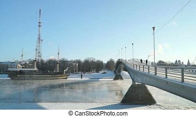 Pedestrian bridge across Volhov river in winter - Pedestrian...