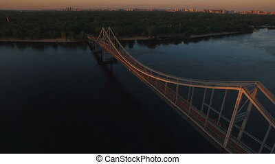 Pedestrian bridge over the river near the city at sunset aerial drone shoot