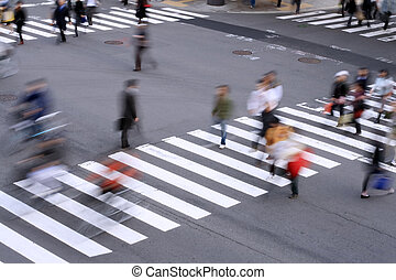 Aspect of a pedestrian cross with motion blurred aspect of the people.