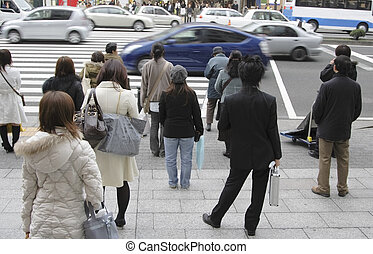 Image of people waiting to cross the street in a big city.