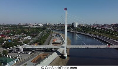 Tyumen, Russia - May 24, 2021: Aerial view onto pesestrian Lovers Bridge during spring period