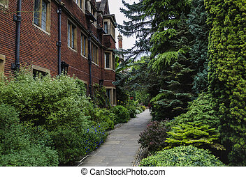 pedestrian path next to the wall of an ancient building with red bricks and green trees, Europe, England