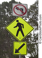 A roadsign warns cars of pedestrians at the top of a blind hill.