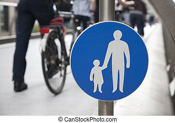 Pedestrian Sign with bicycle and people in the background