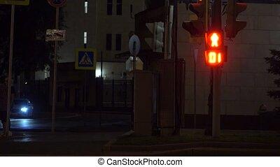 Pedestrian traffic light turns green. Crosswalk at night. 4K shot
