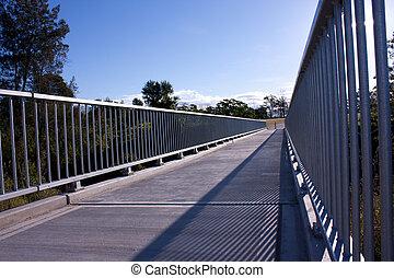 A concrete and steel pedestrian walkway bridge against blue sky