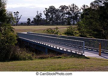 Steel and concrete pedestrian walkway bridge joining two sports fields