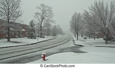 Pedestrians and traffic move down the street during a snow...