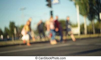 Pedestrians cross the street. Blurred view - Pedestrians...