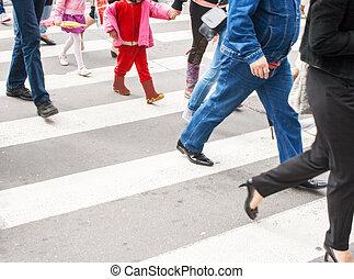 pedestrians in a crosswalk on summer day