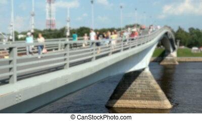 Pedestrians walking on a pedestrian bridge. Summer