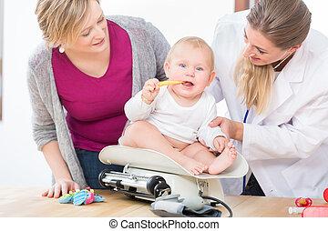 pediátrico, cuidado, especialista, sorrindo, enquanto, medindo, a, peso, de, um, menina bebê