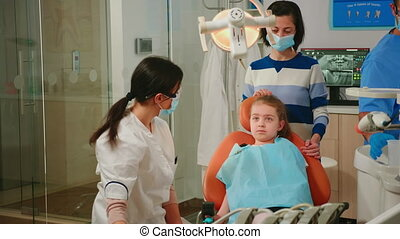 Pediatric dentist and assistant treating girl patient in modern stomatologic clinic. Nurse and doctor wearing protection masks cleaning teeth of child in dental office lying on chair with open mouth