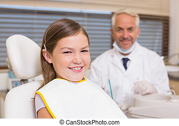 Pediatric dentist and little girl smiling at camera at the...