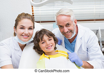 Pediatric dentist assistant and little boy all smiling at...