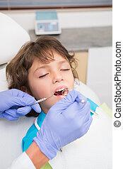 Pediatric dentist examining a little boys teeth in the ...