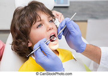 Pediatric dentist examining a little boys teeth in the ...