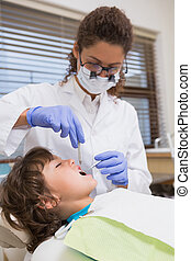 Pediatric dentist examining a little boys teeth in the...