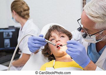 Pediatric dentist examining a little boys teeth with assistant b