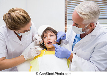 Pediatric dentist examining a little boys teeth with his assista