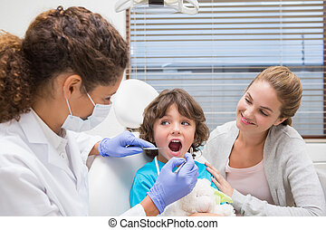 Pediatric dentist examining a little boys teeth with his ...