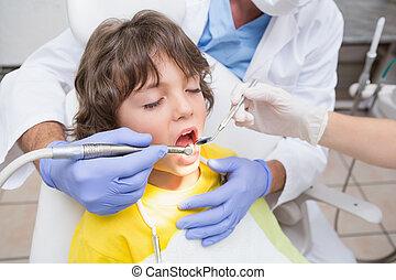 Pediatric dentist examining a little boys teeth in the dentists