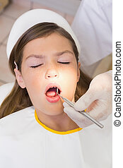 Pediatric dentist examining a patients teeth in the dentists...