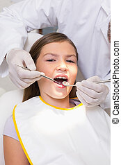 Pediatric dentist examining a patients teeth in the dentists cha