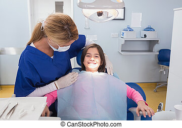 Pediatric dentist examining her smiling young patient