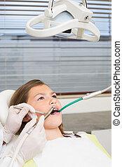 Pediatric dentist examining little girls teeth in the dentists c