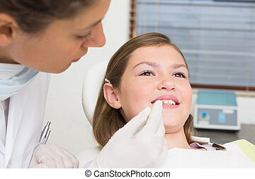Pediatric dentist examining little girls teeth in the dentists c