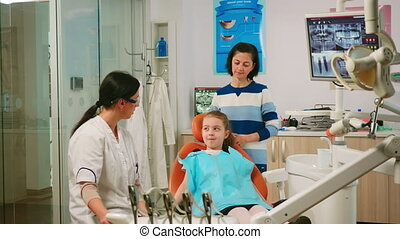 Pediatric dentist explaining to child cleaning process of teeth while man assistant preparing sterilized tools for examination. Nurse and doctor working together in modern stomatological clinic