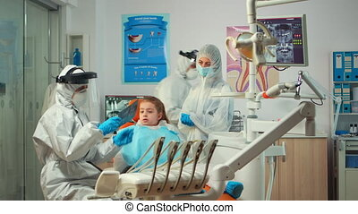 Pediatric dentist wearing protection suit treating girl patient in new normal stomatological unit showing teeth x-ray. Medical team wearing face shield coverall, mask, gloves, explaining radiography