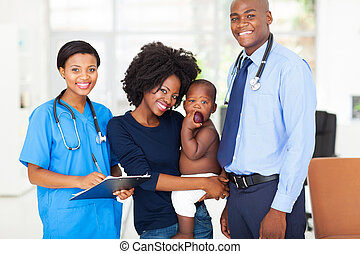 pediatric medical professionals with mother holding her baby