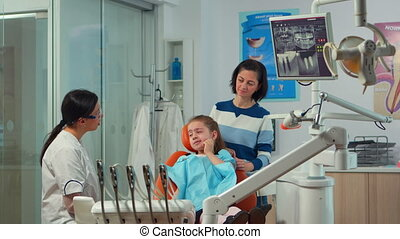 Pediatric woman dentist talking with mother and girl about eating habit and oral hygiene of the child before dental examination. Sad kid patient is showing sick tooth while nurse preparing dental tools