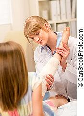Pediatrician checking broken bandage girl leg