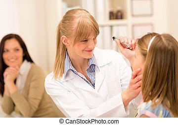 Pediatrician checking eye girl at medical office