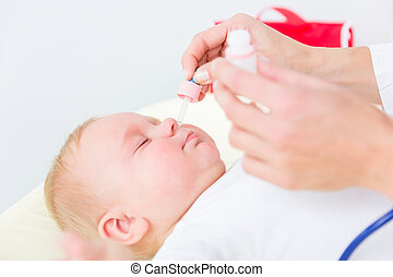 Pediatrician clearing the nose of a baby by applying saline solution