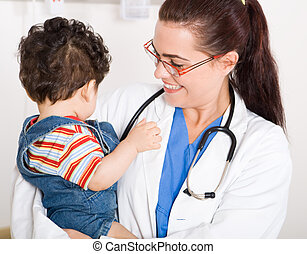 Young female pediatrician holding a baby boy patient