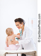 Pediatrician doctor examine kid using stethoscope