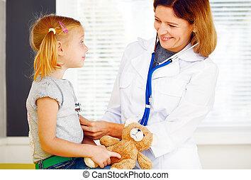 Pediatrician doctor examining little girl.
