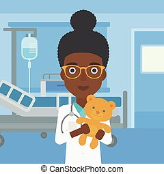 Pediatrician doctor holding teddy bear.