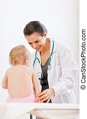 Pediatrician doctor playing with baby on survey