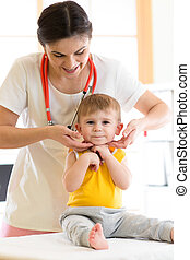 Pediatrician doctor touching the throat of kid patient in...