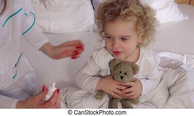 Pediatrician doctor using nasal spray for stuffy nose cute...