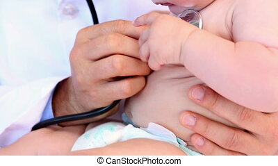 Pediatrician examining baby boy in his office at the...