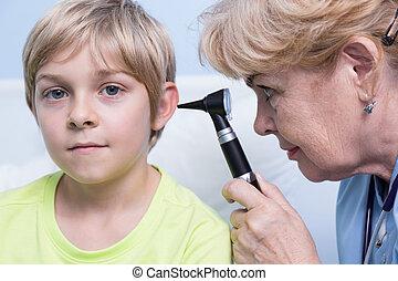 Pediatrician examining ear - Senior pediatrician examining...