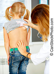 Pediatrician examining little girl with back problems.