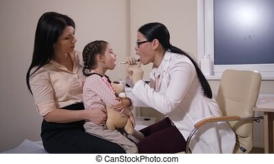 Pediatrician examining throat of sick little girl