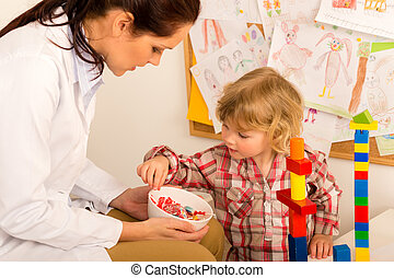 Pediatrician give lolly to little child girl